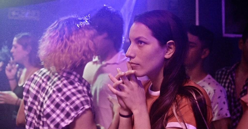 Iris (Sofia Cabrera) in a club, watching something.