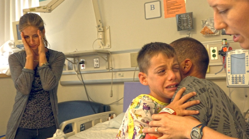 Ron crying in his hospital bed, clinging to his father. His mother is standing in the background, covering her face with her hands.