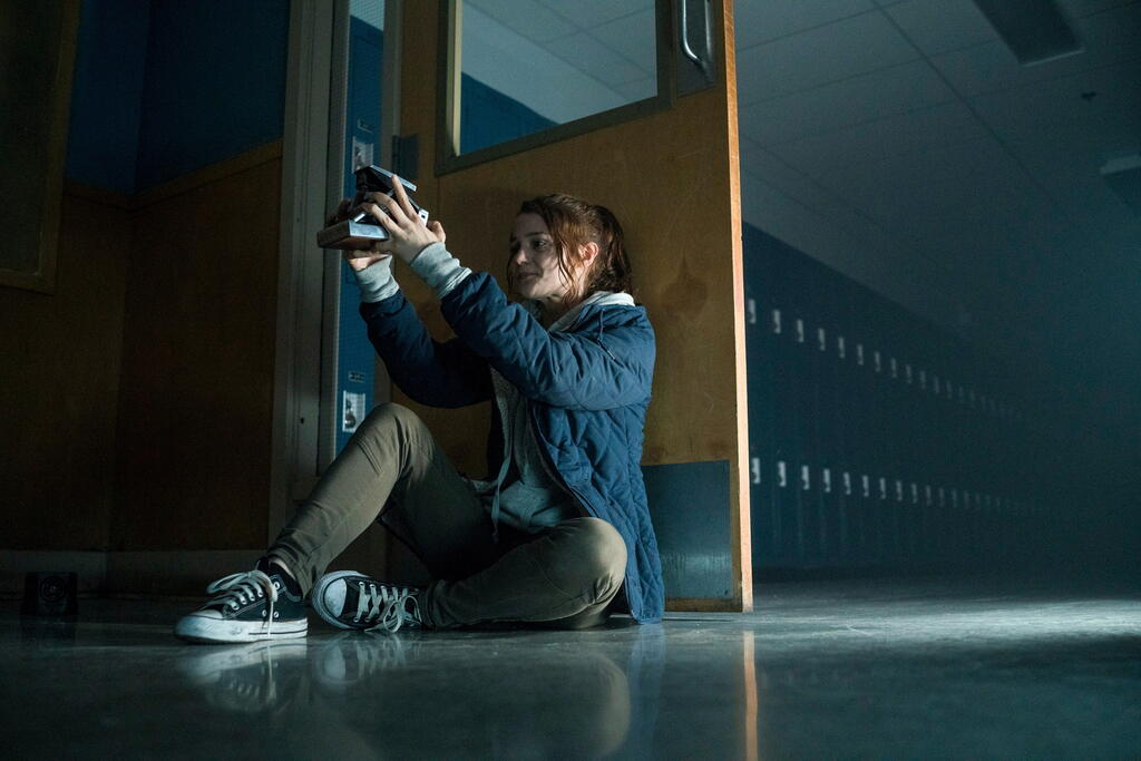 Bird (Kathryn Prescott) hiding behind a door as she takes a picture of herself with the polaroid camera.