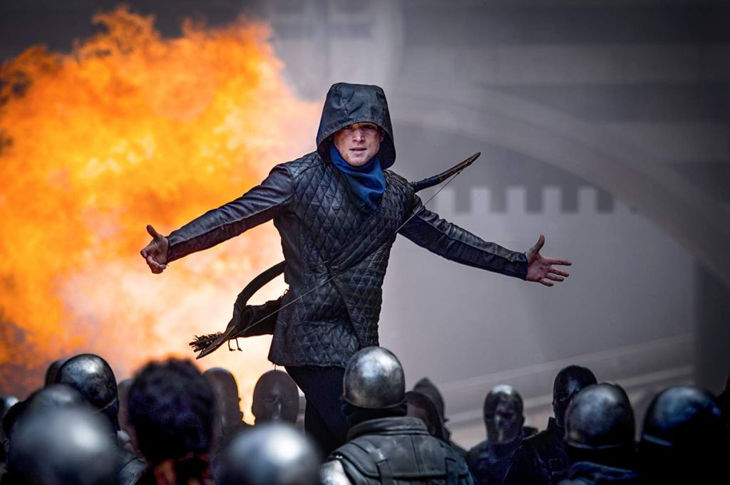 Robin (Taron Egerton) taunting a group of soldiers. There's an explosion in the background.