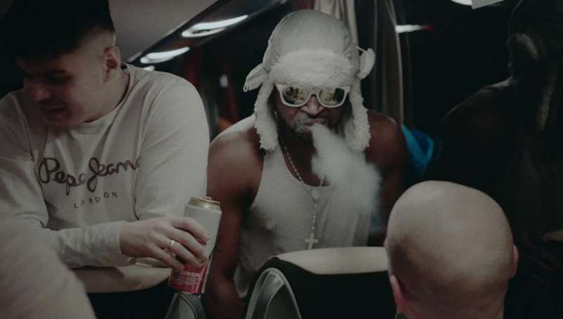 Two of Robin's players smoking and drinking on a bus.