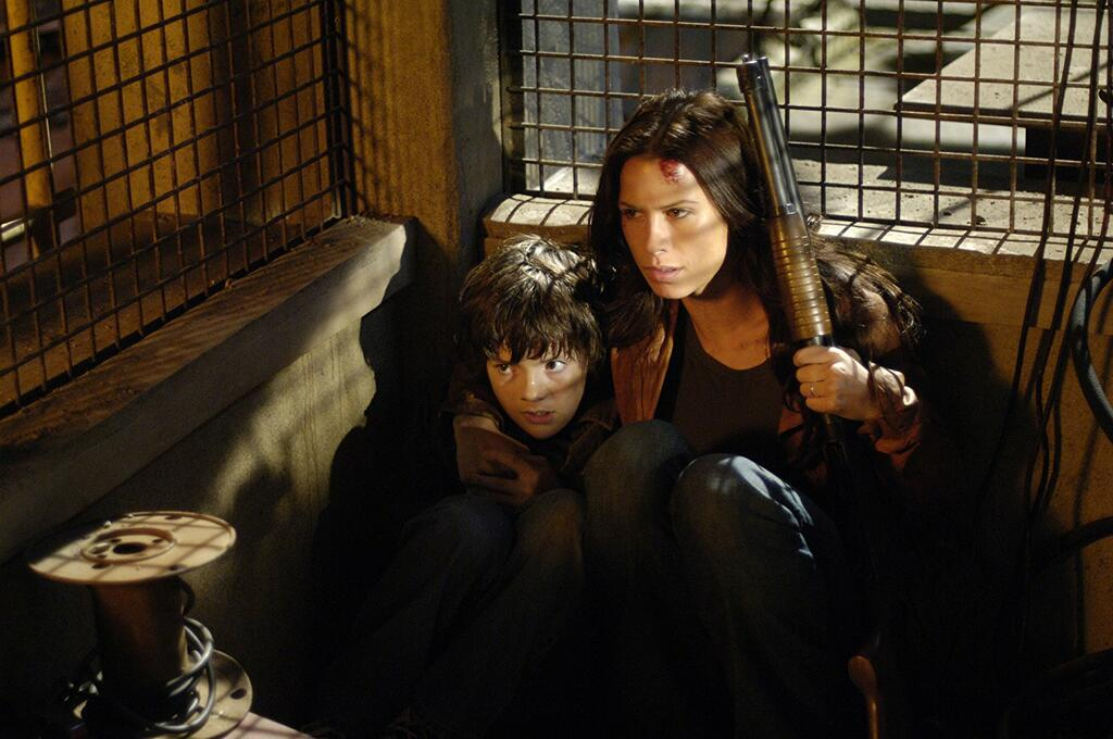 Rachel (Rhona Mitra) cowering in a cage with her son Timothy (Matthew Knight).