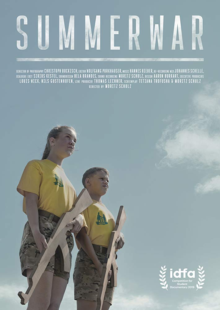 The film poster showing Jasmin and Jastrip in military style shorts and yellow shirts, cradling wooden machine guns.