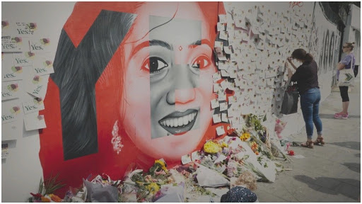 A mural of Savita Halappanavar surrounded by lots of messages on paper.