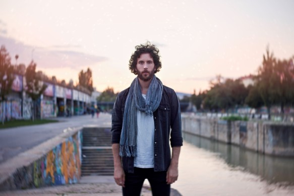 A single guy in a scarf standing next to the danube in the sunset.