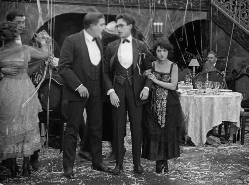 The boy (Harold Lloyd) at a party, a girl clutching his arm.