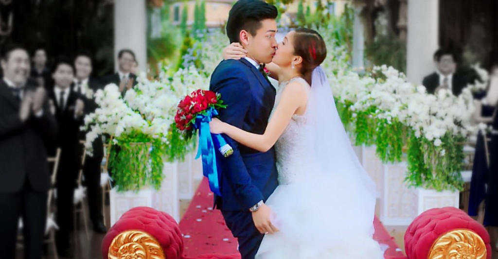 Rocky (Kim Chiu) kissing Rocco (Xian Lim) at their wedding, with Rocco looking very surprised.