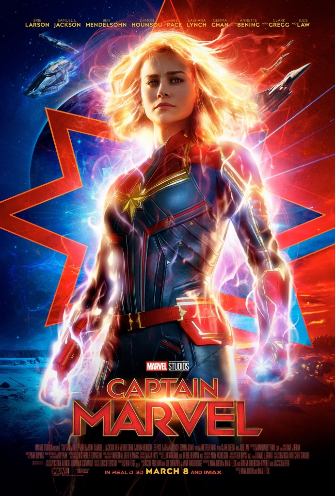 The film poster showing Vers/Carol Danvers (Brie Larson) in her Captain Marvel outfit, energy flowing through her.