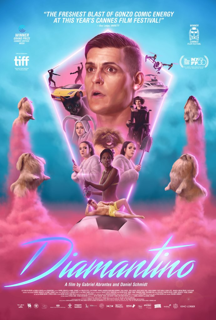 The film poster showing a pink diamond shape emerging from a soccer ball that is placed in pink mist. Four dogs are rising next to the shape on pink clouds like rockets. within the shapes are the main characters of the film, biggest Diamantino (Carloto Cotta) with a stunned facial expression.