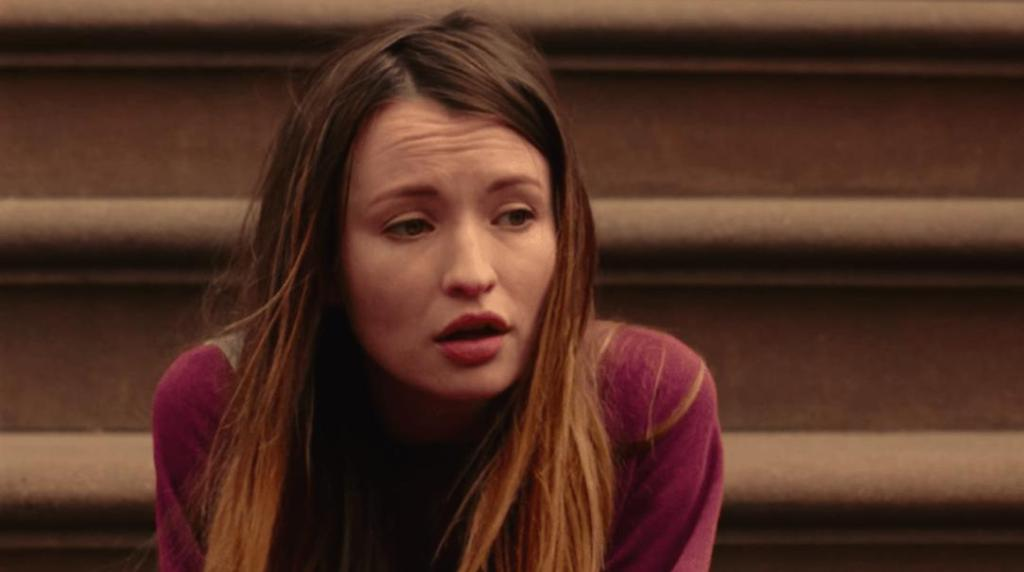Naomi (Emily Browning) sitting on some stairs outside.