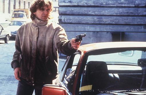 Robert (Hansi Lang) pointing a gun at someone or something.