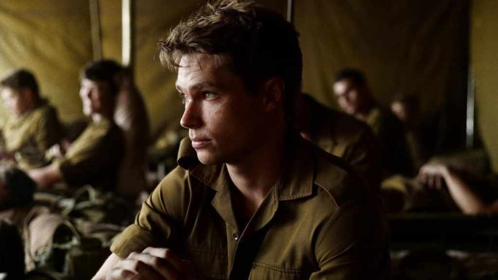Nicholas (Kai Luke Brummer) in a tent with other soldiers.