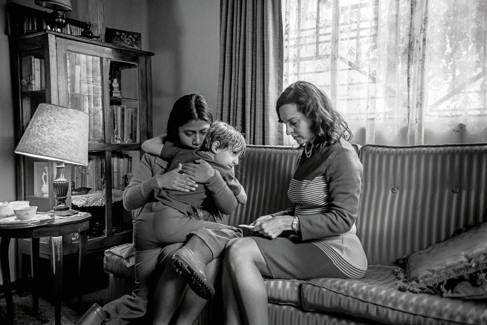 Cleo (Yalitza Aparicio) sitting next to Sra Sofía (Marina de Tavira) on the sofa, hugging Sofía's son Pepe (Marco Graf).