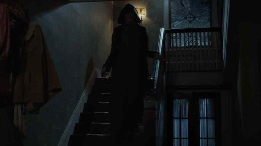The Bye Bye Man (Doug Jones) - a hooded figure whose face you can't see - coming down the stairs.