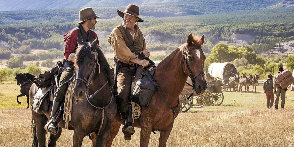 Charlie (Joaquin Phoenix) and Eli Sisters (John C. Reilly) on horseback in front of a waggon caravan.