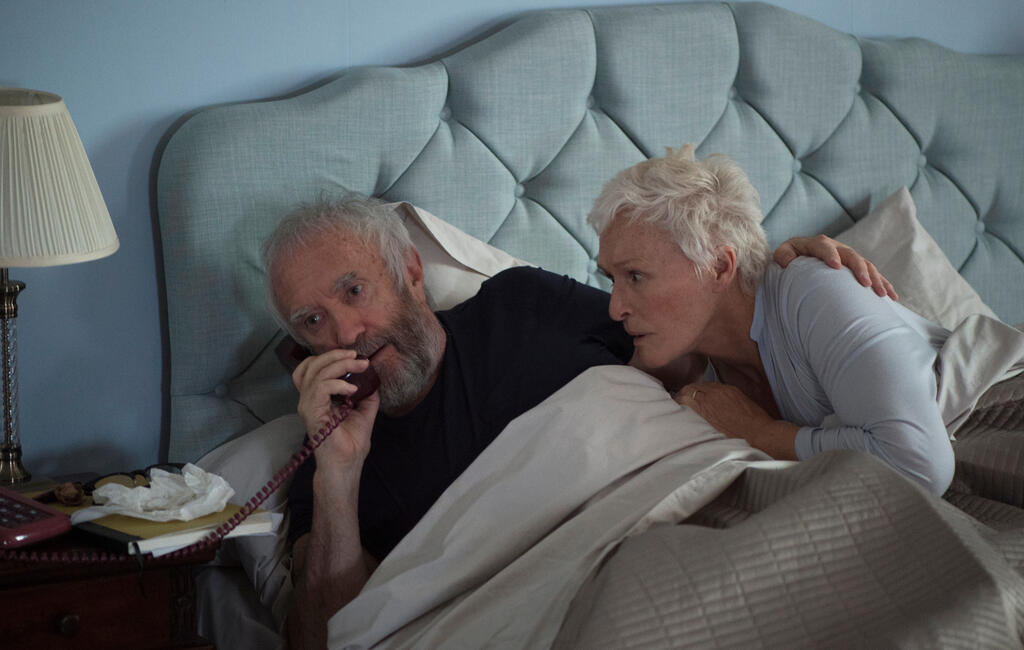 Joe (Jonathan Pryce) and Joan (Glenn Close) in bed. Joe is on the phone, Joan is anxiously listening to the call.