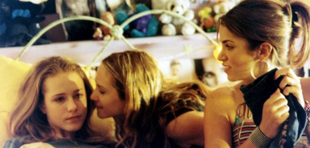 Mel (Holly Hunter) leaning in to kiss her daughter Tracy (Evan Rachel Wood) who is lying on her bed. Next to them on the bed sits Evie (Nikki Reed), holding a pair of jeans.