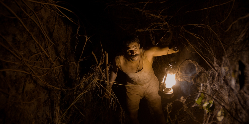 Vinayak (Sohum Shah) in a hole, surrounded by roots.
