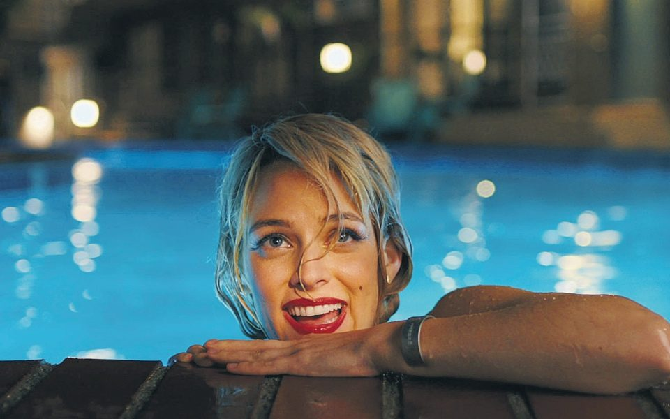 Sarah (Riley Keough) holding on to the edge of the pool, smiling.