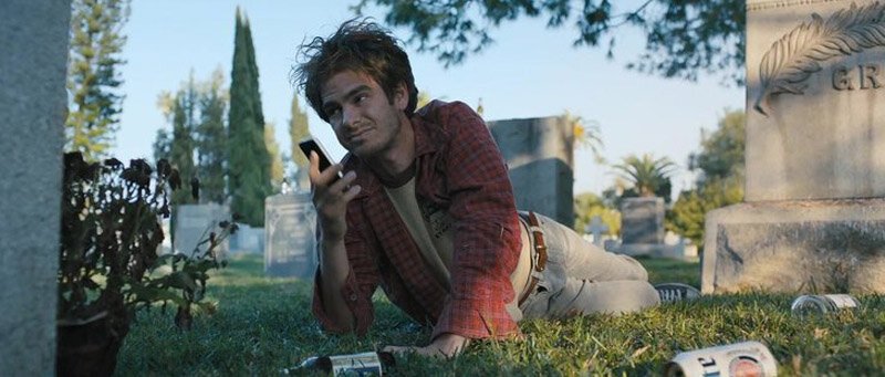 Sam (Andrew Garfield) lying in a graveyard.