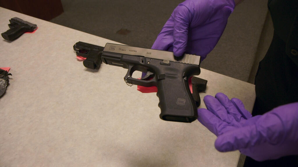 Two hands in violet plastic gloves showing off a handgun.