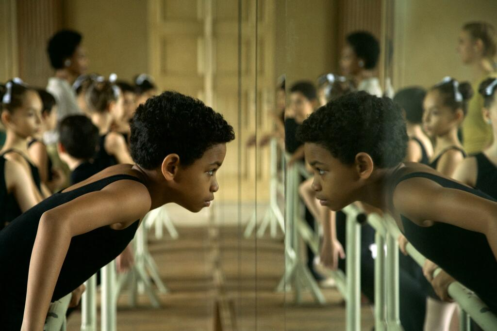 Young Carlos (Edlison Manuel Olbera Núñez) looking at himself in the mirror in the ballet studio.