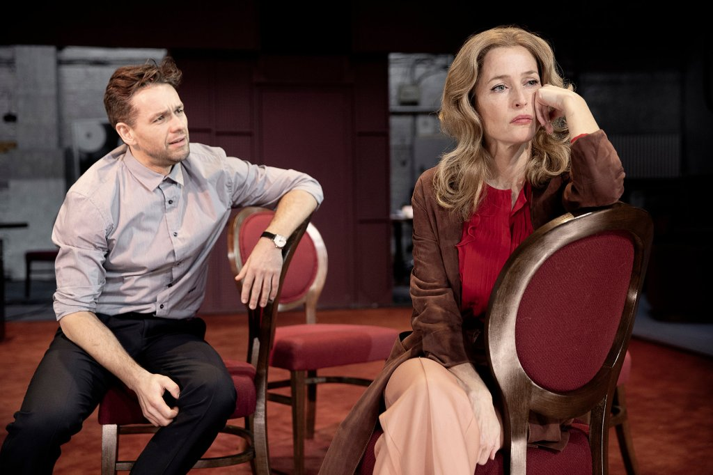 Margo (Gillian Anderson) sitting on a chair, looking pensive. Behind her sits Bill (Julian Ovenden), trying to talk to her.