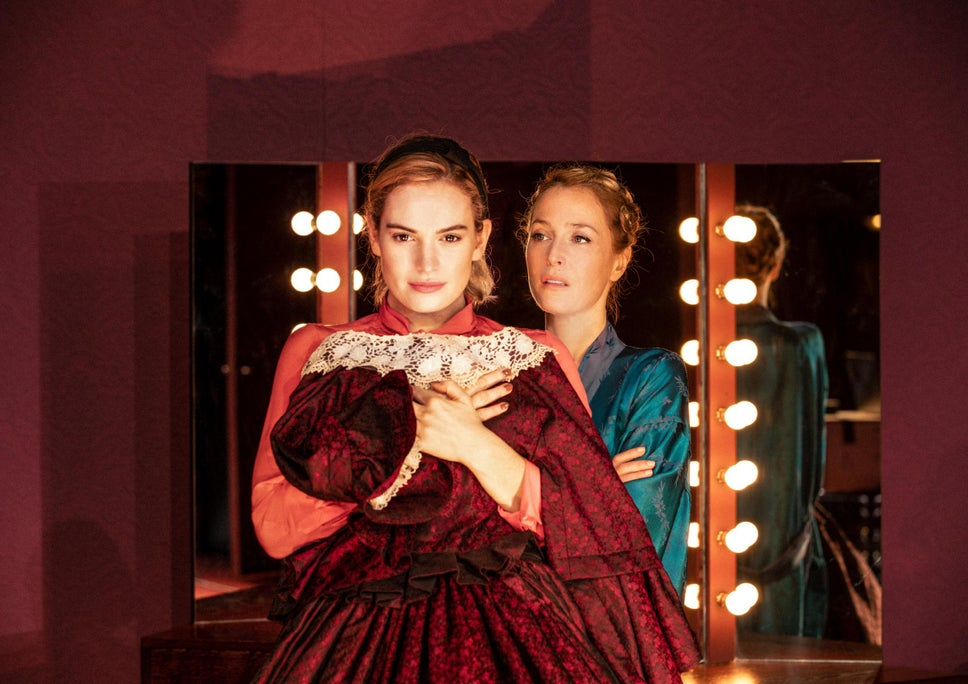Eve (Lily James) holding a dress against her chest, as Margo (Gillian Anderson) stands behind her.