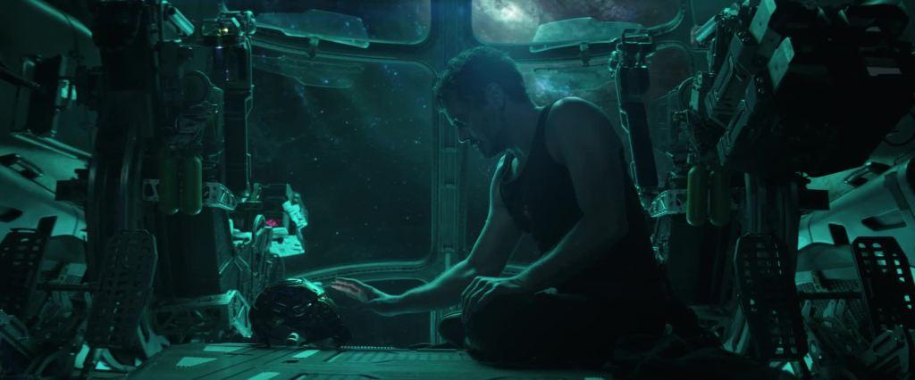 Tony Stark (Robert Downey Jr.) sitting in a spaceship, reaching for his Iron Man helmet.