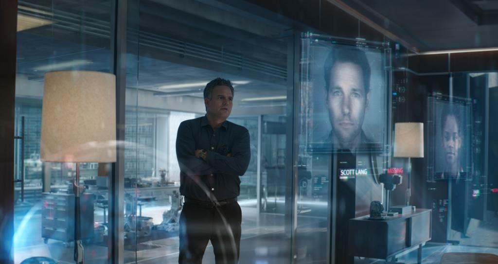 Bruce Banner (Mark Ruffalo) standing next to two screens showing Scott Lang (Paul Rudd) and Shuri (Letitia Wright).