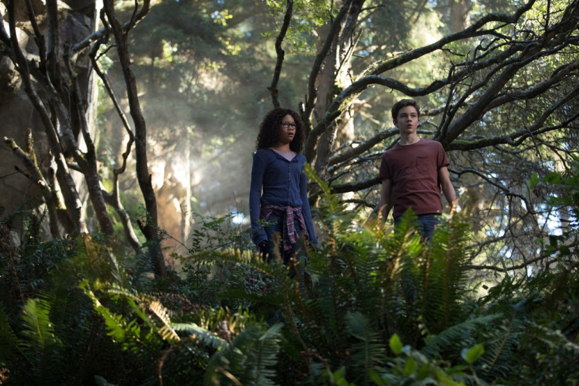 Meg (Storm Reid) and Calvin (Levi Miller) in a forest.