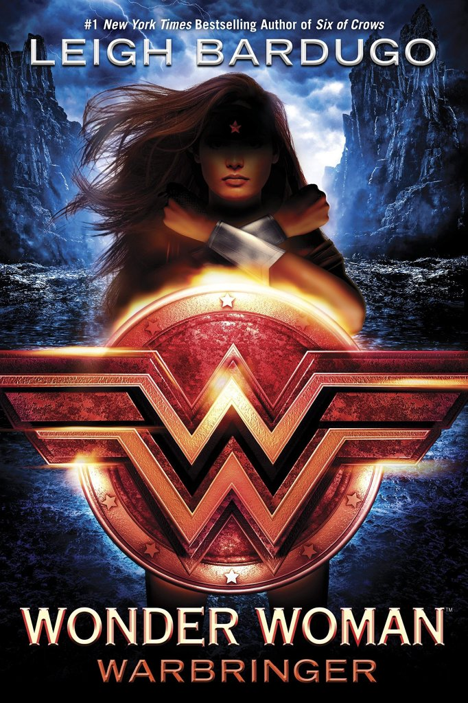 The book cover showing Wonder Woman, her hair blowing in the wind, her face shadowed, her arms crossed in front of her chest behind a shield with her emblem.