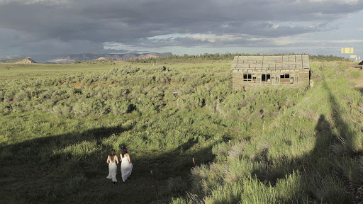 Sarah (Sarah Small) and Isolde (Isolde Chae-Lawrence) walking over a meadow towards a ramshackle shed in white dresses.