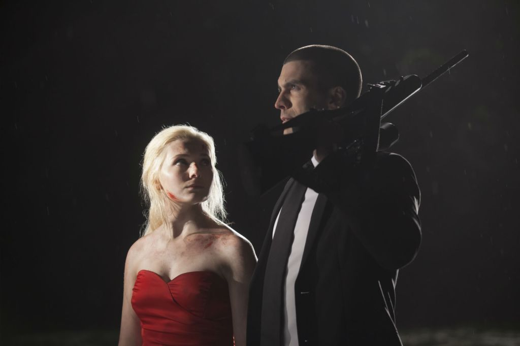 Veronica (Abigail Breslin) looking up at William (Wes Bentley) who has a gun over his shoulder.
