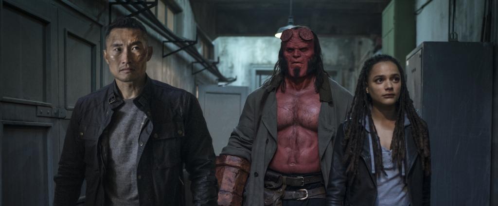 Ben Daimio (Daniel Dae Kim), Hellboy (David Harbour) and Alice Monaghan (Sasha Lane) walking down a corridor.