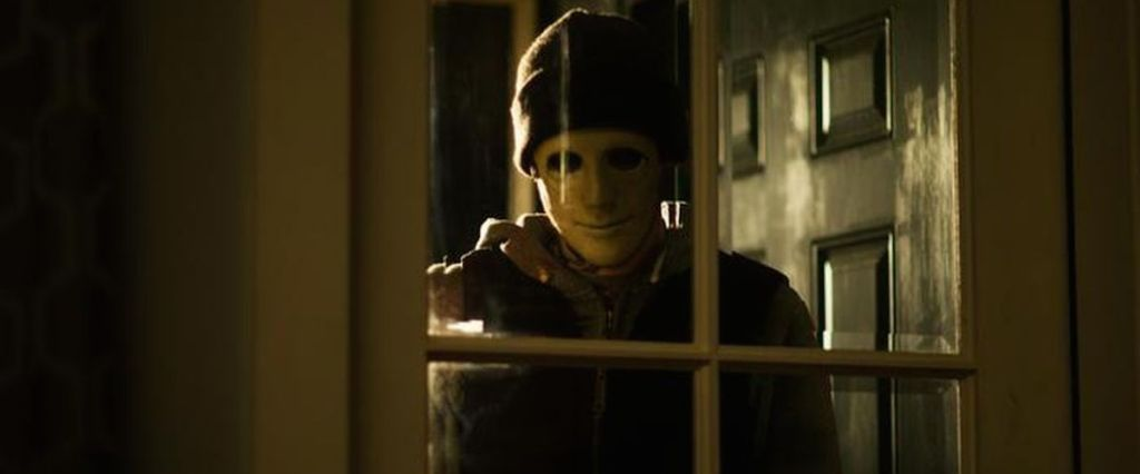 A masked man (John Gallagher Jr.) looking through a glass door into the house.