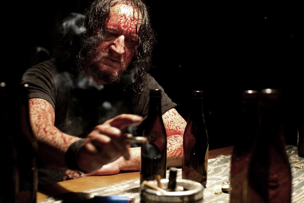 Karl (Andreas Sobik) sitting blood-spattered at a table.