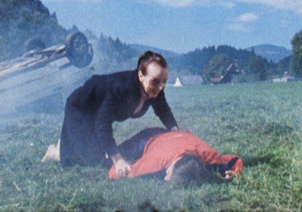 The mother (Greta Kostka) leaning over the body of her daughter Karin (Andrea Maier) next to a car wreck.