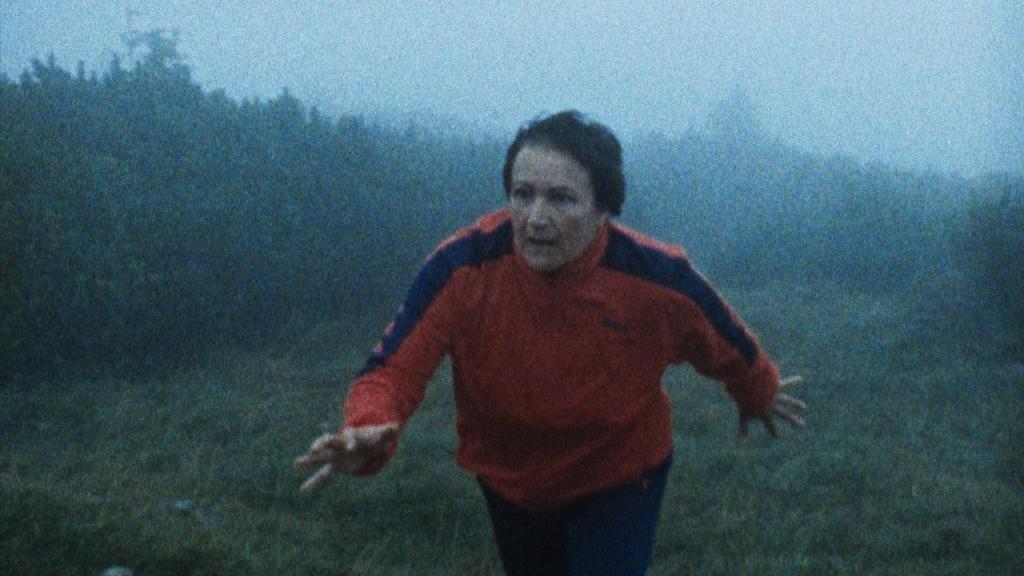 Karin (Andrea Maier) running through a foggy field.
