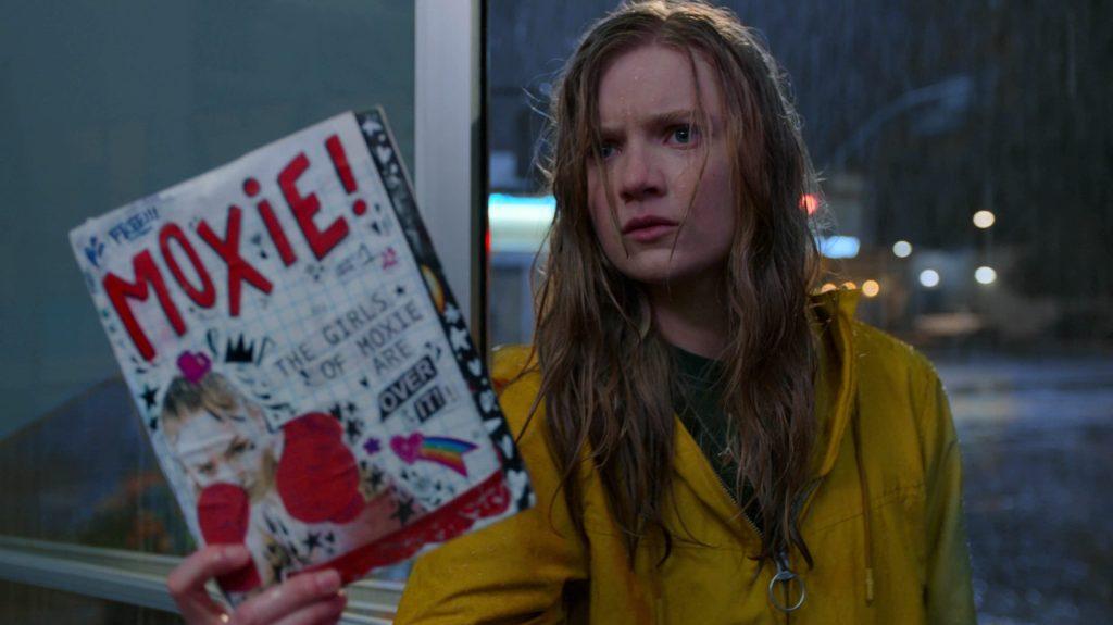 Vivian (Hadley Robinson) holding up a copy of the Moxie zine.