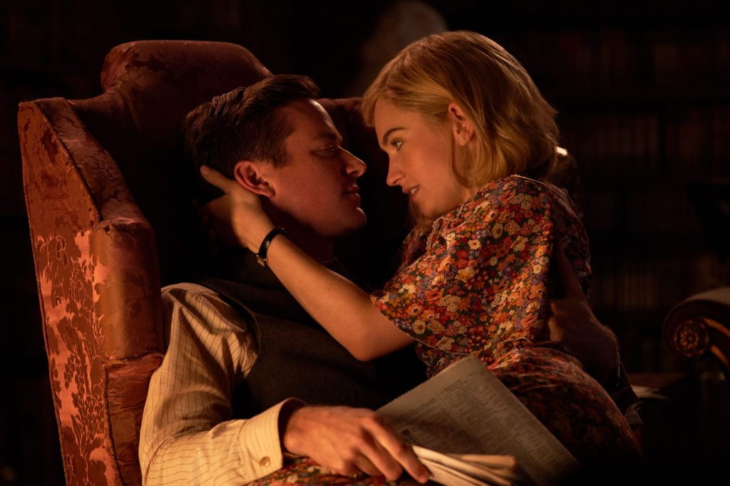 The protagonist (Lily James) sitting in Maxim's (Armie Hammer) lap.