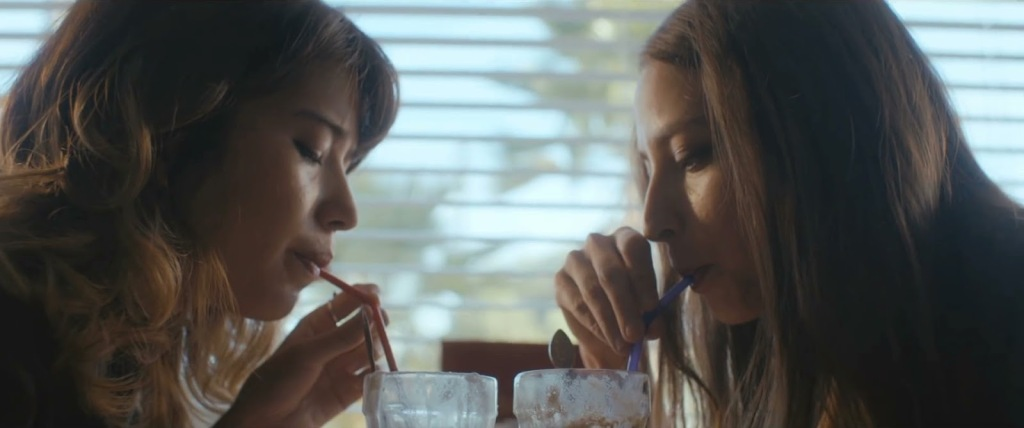 Annie (Nichole Sakura) and Jules (Fabianne Therese) drinking milkshakes together.