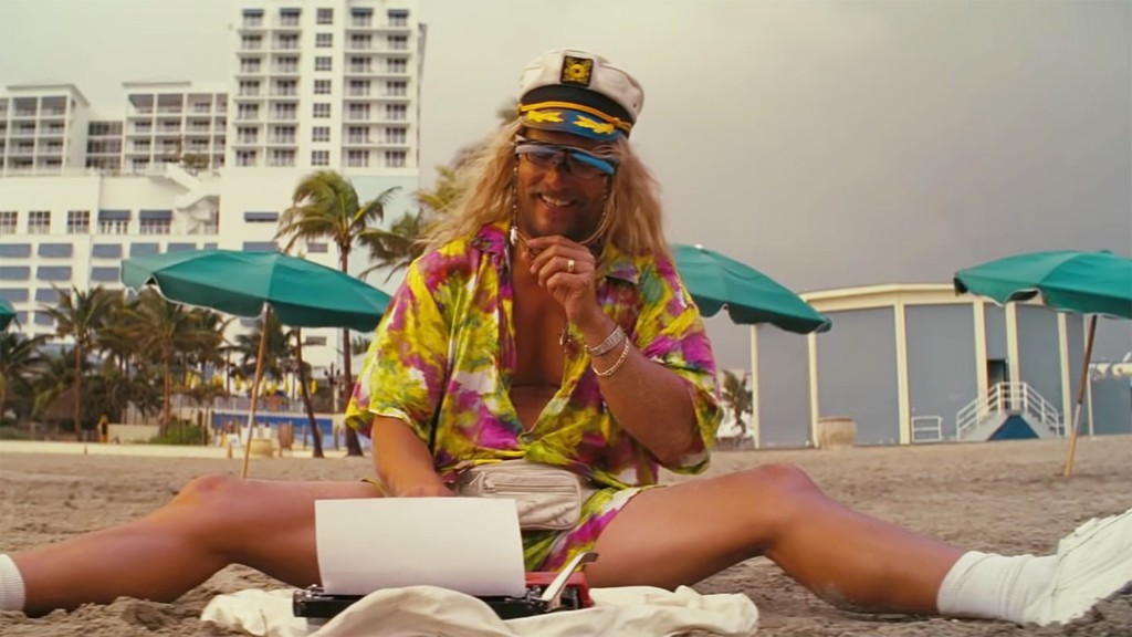 Moondog (Matthew McConaughey) sitting on the beach in a floral dress and a captain's hat with a typewriter in front of him.