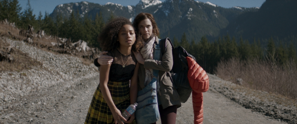 Lizzie (Logan Browning) leaning on Charlotte (Allison Williams) as they walk down a road in the middle of nowhere.