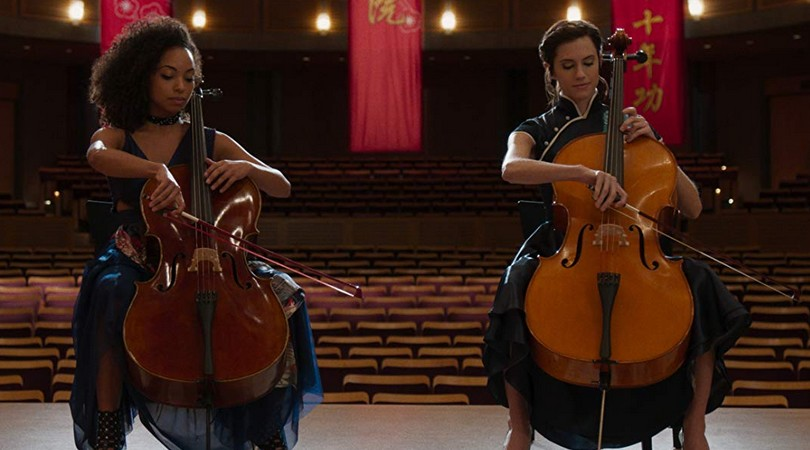 Lizzie (Logan Browning) and Charlotte (Allison Williams) playing a duet on their cellos.