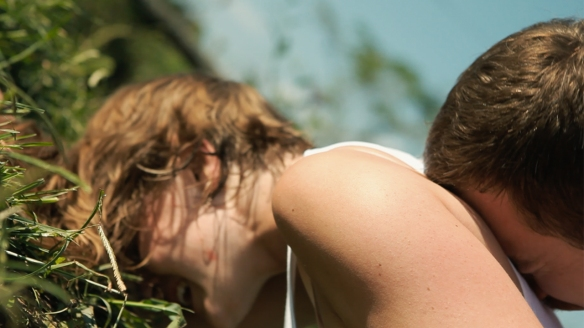Sarah (Sophie Traub) pressed face-down into the grass with Akin (Joe Swanberg) lying on top of her.