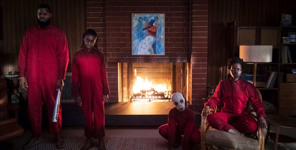 Abraham (Winston Duke), Umbrae (Shahadi Wright Joseph), Pluto (Evan Alex) and Red (Lupita Nyong'o), all wearing red overalls, standing and sitting in strange poses in the living room.