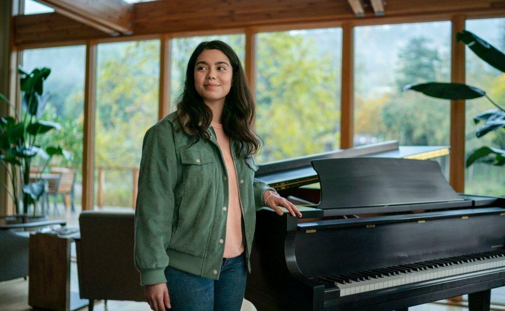 Amber (Auli'i Cravalho) standing next to a piano.