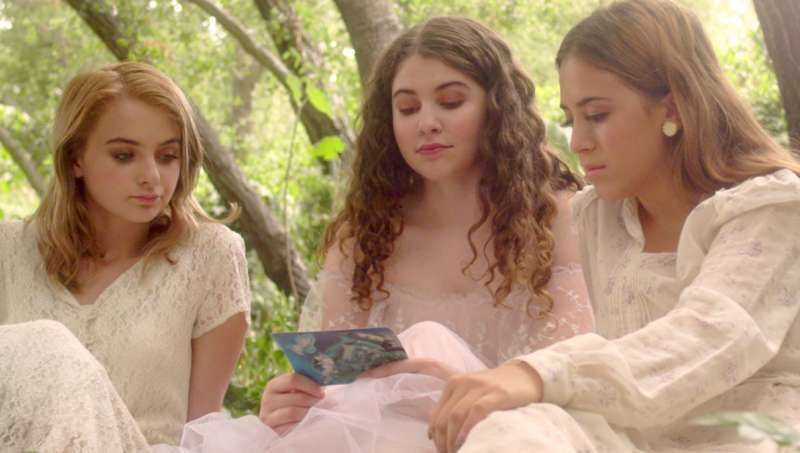 Haley (Haley Bodell), Gwen (Audrey Boos) and Trish (Gabriella Herrera) reading a postcard together, all dressed in white, sitting in the forest.