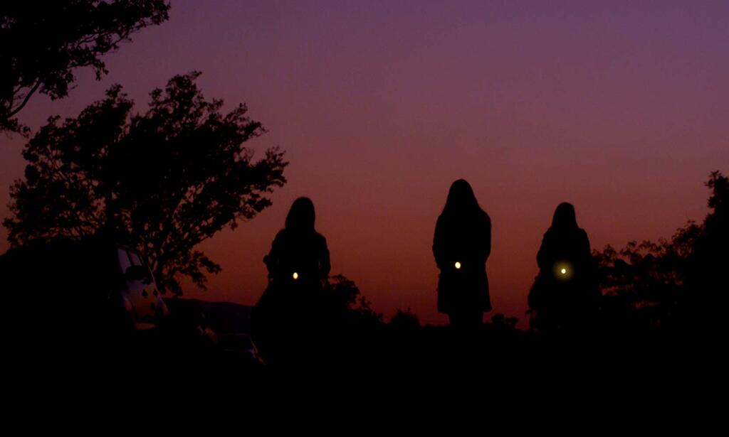 Three girls walking with flashlights. They can just be seen as silhouettes against the sunset.